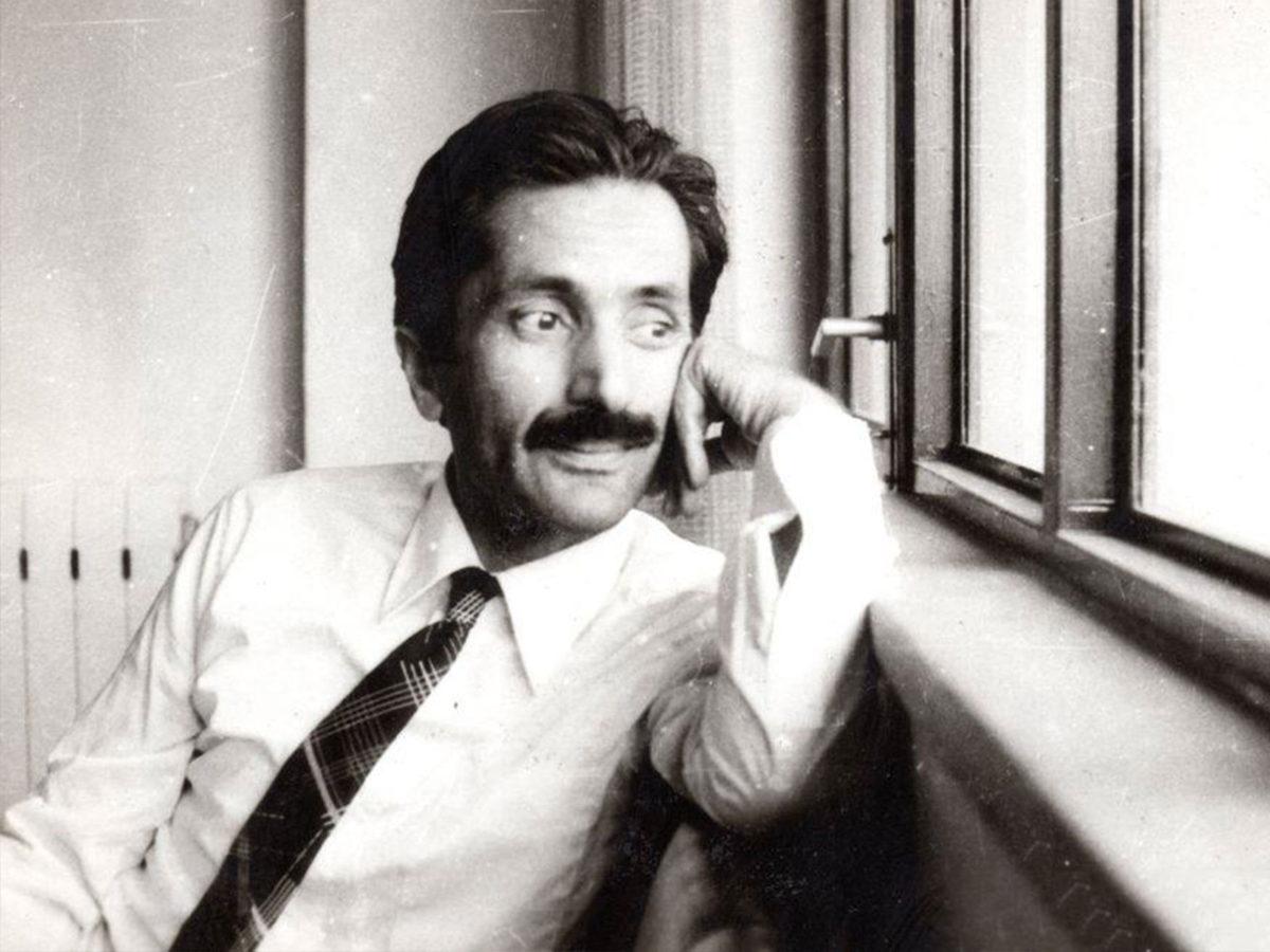 Cahit Zarifoğlu kırklı yaşlarında, kıravat, gömlek, sol elini yanağına dayamış, pencereden dışarı bakıyor