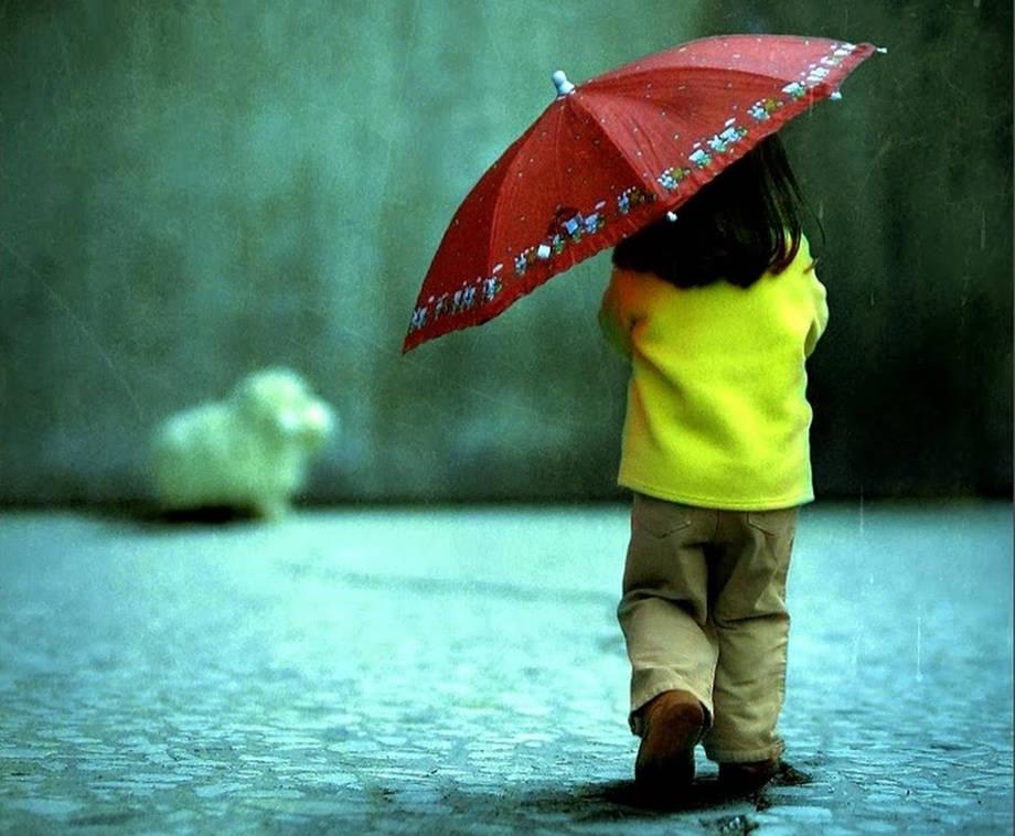 Elinde şemsiye, yağmur altında yürüyen, siyah saçlı, saçları omzuna dökülen, üstünde açık yeşil polar ceketi olan, altında kahverengi pantolonu olan küçük bir kız